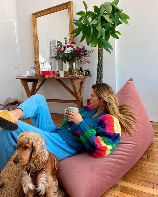Девушка в уютной домашней атмосфере в свободных синих штанах и вязанном свитере