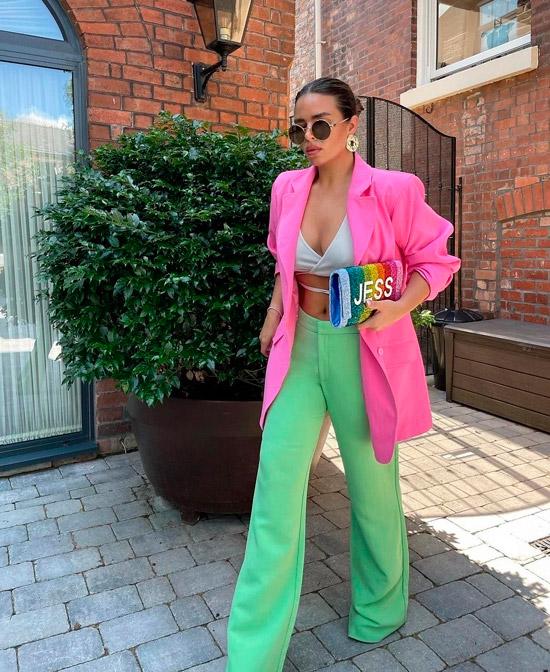 Девушка в зеленых брюках клеш, белый топ и розовый пиджак оверсайз
