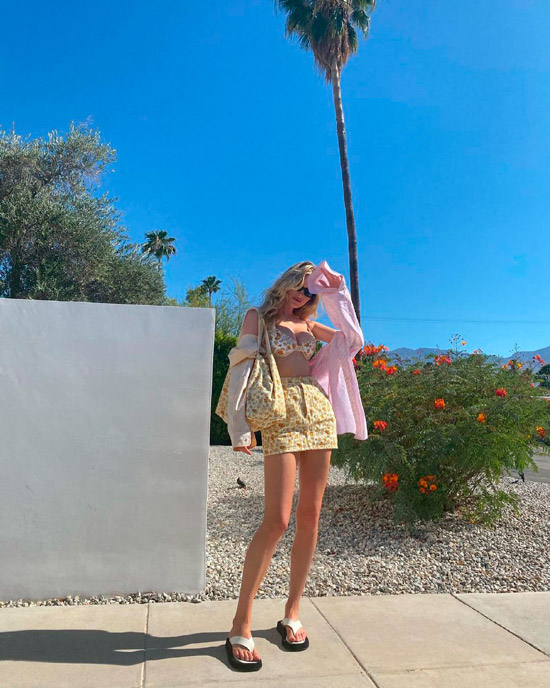 Девушка в желтой мини юбке, розовая рубашка оверсайз и сандалии на толстой подошве