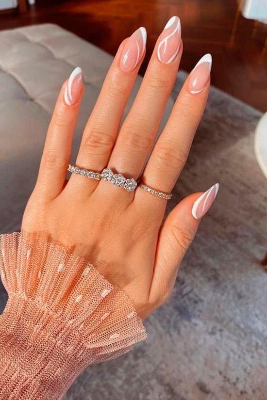 Интересный натуральный маникюр с белыми волнистыми линиями на миндальных ногтях