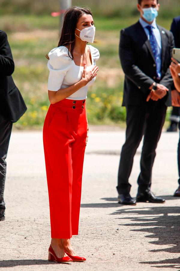 Королева Летиция в красных брюках и белой блузе