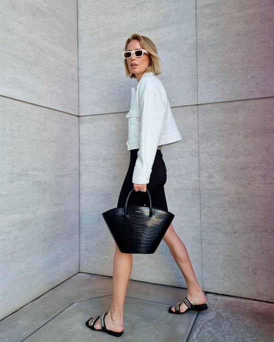 Модель в белой укороченной куртке, облегающие черные шорты, образ дополняют черные сланцы, сумка и солнцезащитные очки в белой оправе