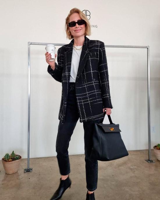 Модель в простых джинсах, белая футболка, черный блейзер осверсайз, образ дополняют ботильоны, черная сумка и очки