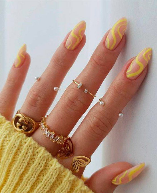 Натуральный маникюр с желтыми волнистыми линиями на длинных миндальных ногтях