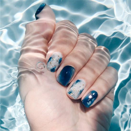 Синий морской маникюр с золотой фольгой на ногтях средней длины