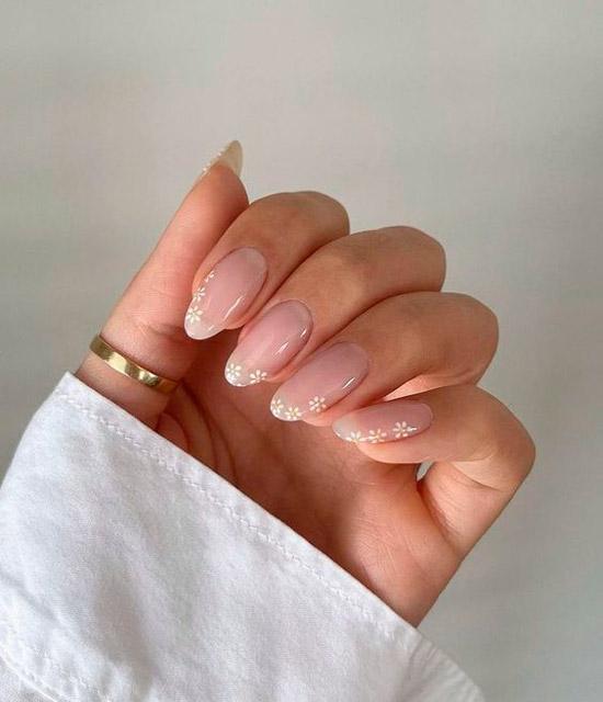 Светлый натуральный маникюр с мелкими белыми цветами на длинных овальных ногтях