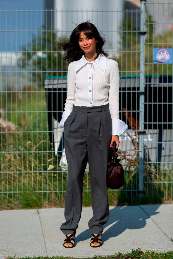 Девушка в серых брюках и белой блузе