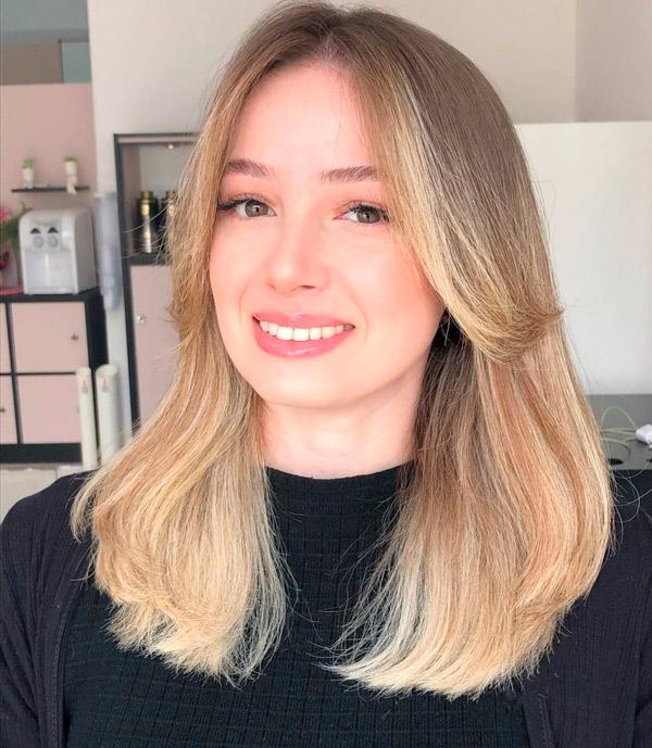 Пышная прическа на русых волосах с челкой