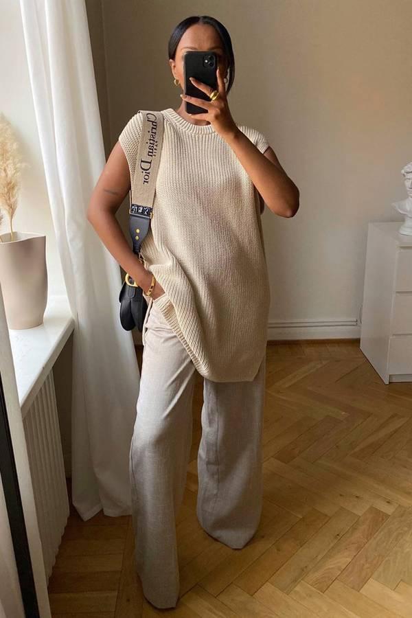 Девушка в белых свободных брюках и светлом вязанном жилете