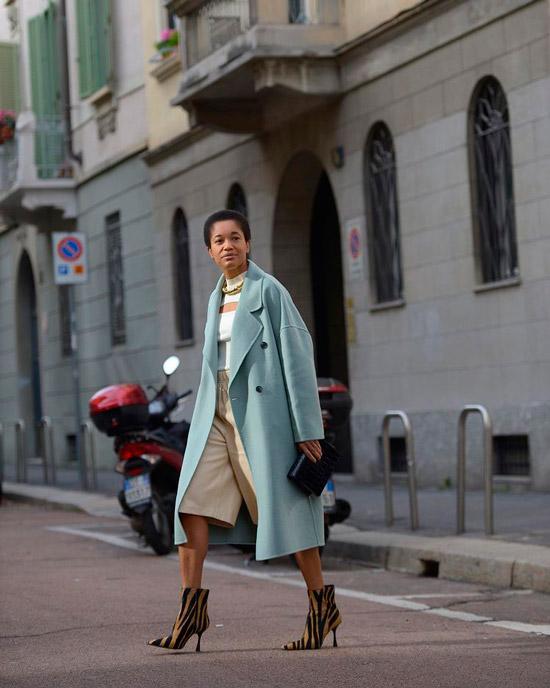 Девушка в бермудах, голубом пальто и необычных ботильонах на каблуке