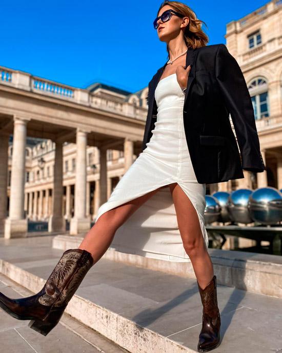 Девушка в бежевом платье комбинации, коричневых ковбойских сапогах и черном жакете