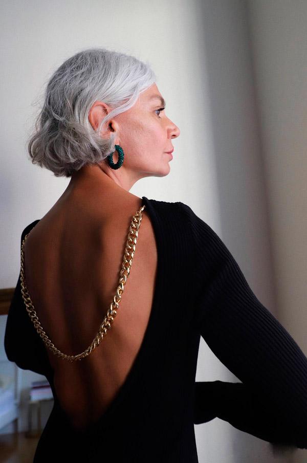 Женщина в черном трикотажном платье с открытой спиной и золотой цепью