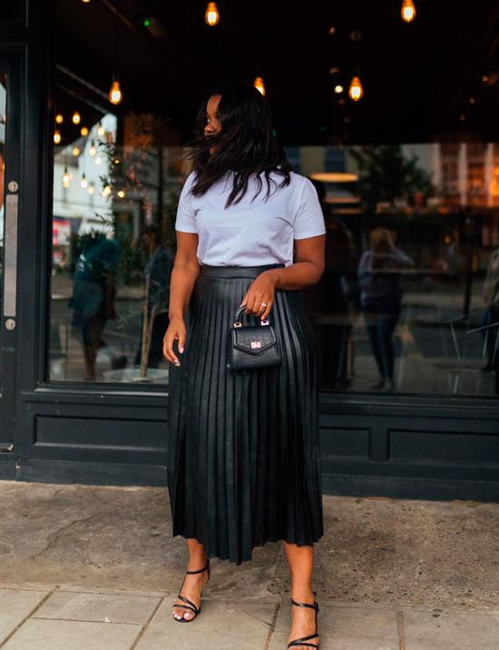 Девушка в черной плиссированной юбке, белой футболке и босоножках на ремешках