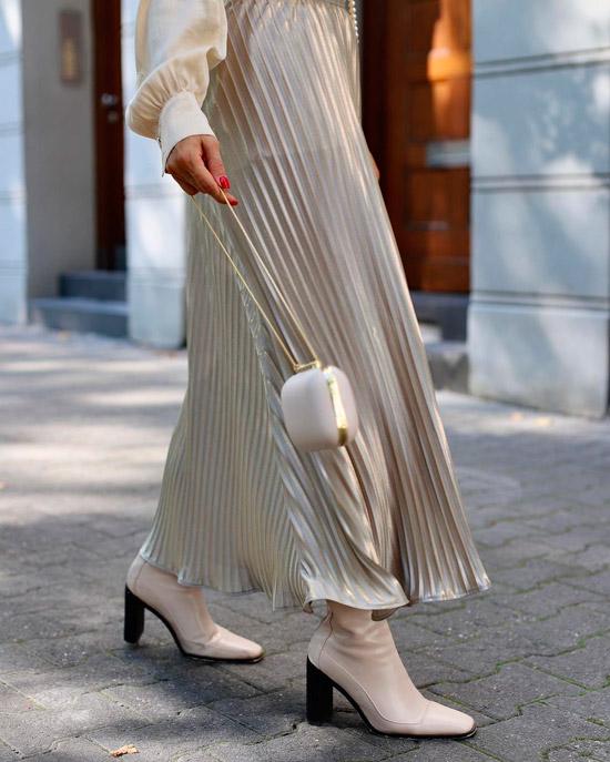 Девушка в длинной плиссированной юбке, блузке и белых сапогах