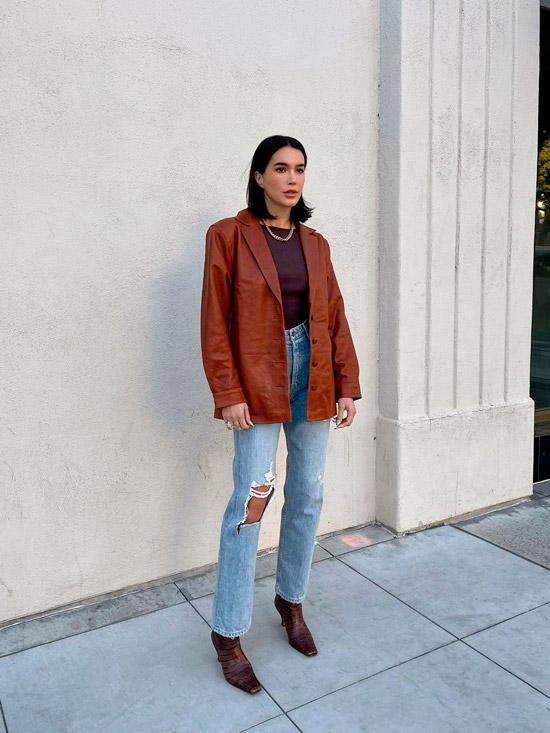 Девушка в голубых джинсах, коричневой кожаной куртке и ботильонах