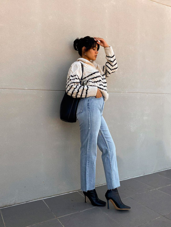 Девушка в голубых джинсах, сером свитере в полоску и черных ботильонах на шпильке