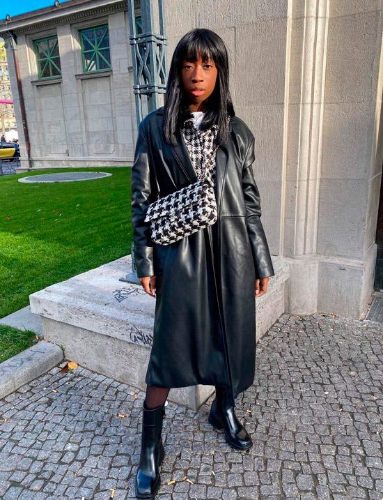 Девушка в кожаном плаще, черных ботильонах на толстом каблуке и сумочкой с принтом