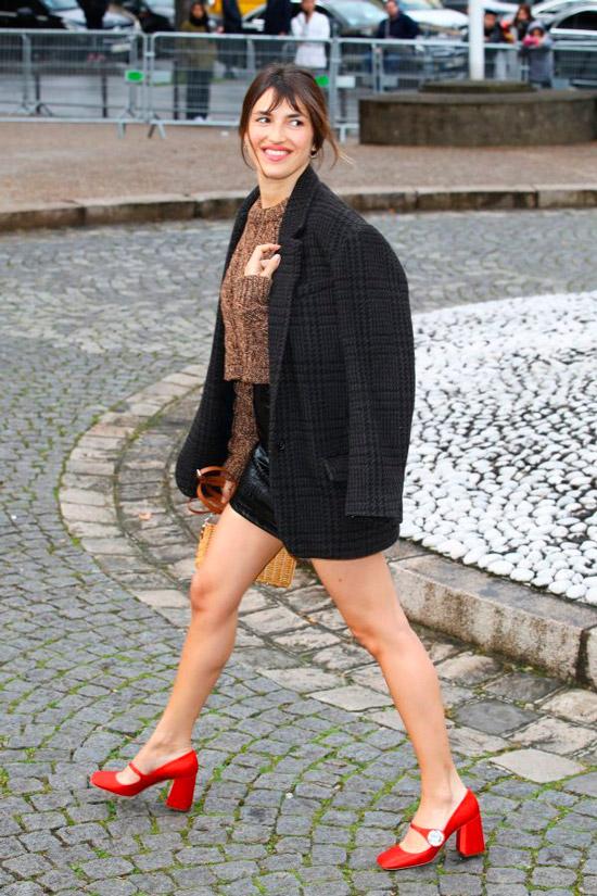 Девушка в кожаной мини юбке, жакете оверсайз в клетку и красных туфлях Mary Jane