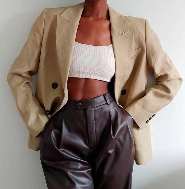 Девушка в кожаных брюках с высокой талией и бежевом пиджаке