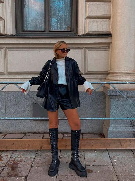 Девушка в кожаных шортах, черной рубашке и высоких сапогах на шнуровке