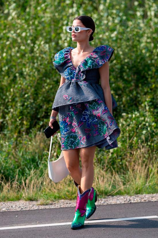 Девушка в необычном синем платье и разноцветных ковбойских сапогах
