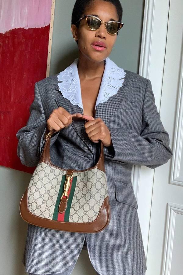 Девушка в сером пиджаке в тонкую клетку и модной сумочкой
