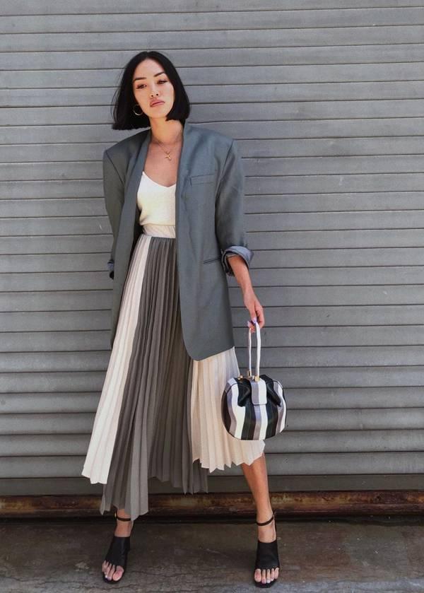 Девушка в серой плиссированной юбке миди и оверсайз пиджаке