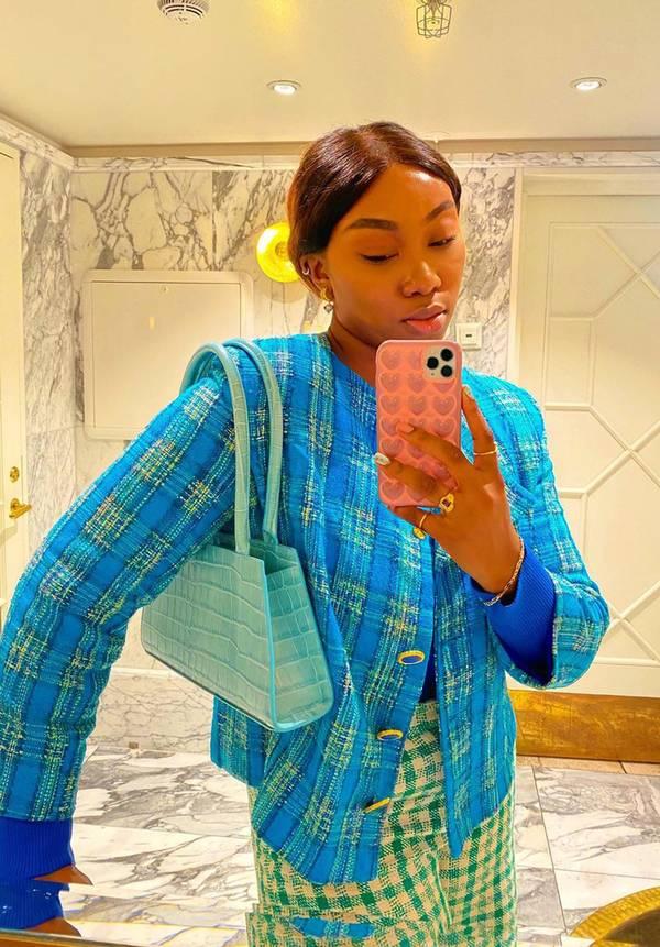 Девушка в синем жакете в клетку и бирюзовой сумочкой