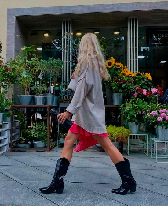 Девушка в свитере оверсайз, мини юбке и лакированных ковбойских сапогах