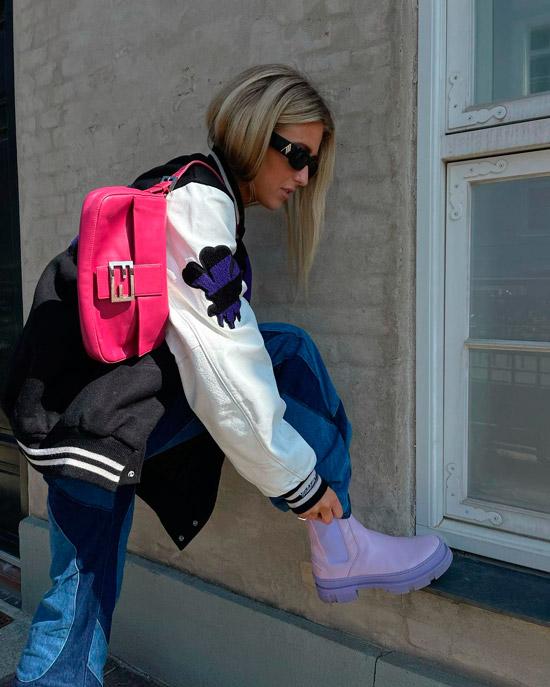 Девушка в свободных джинсах, спортивной куртке и интересных фиолетовых ботинках