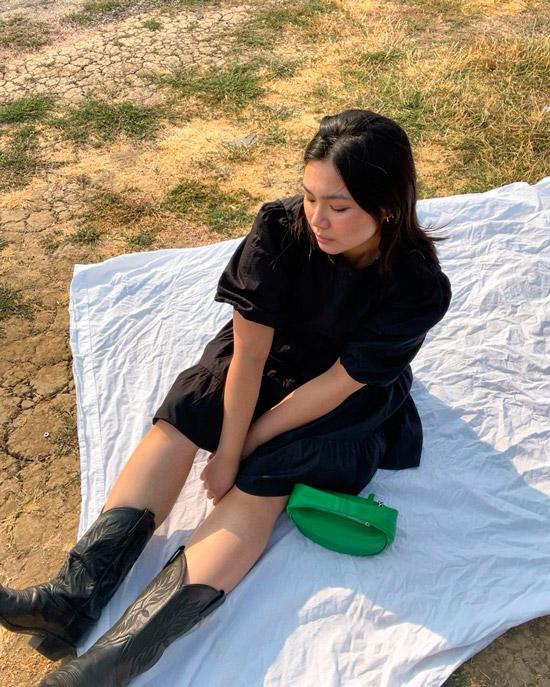 Девушка в воздушном черном платье и ковбойских сапогах