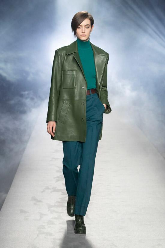 Девушка в зеленной удлиненной куртке, прямых брюках с ремнем и водолазке