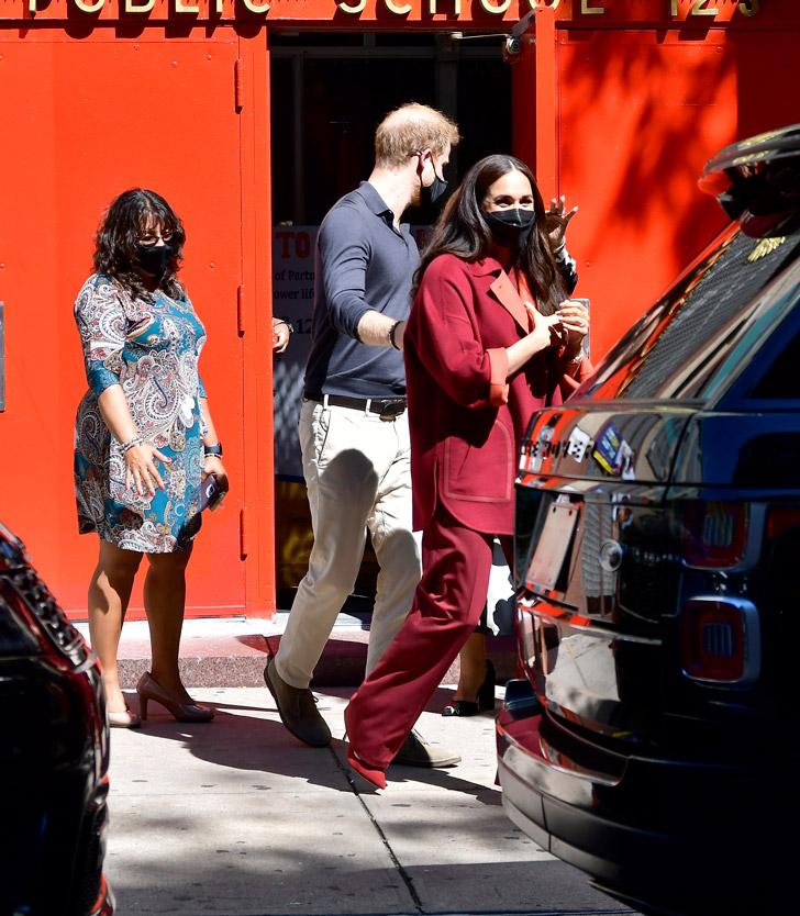 Меган Маркл в бордовом пальто и широких брюках