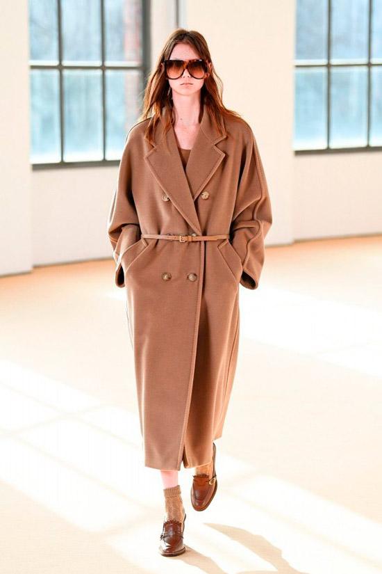 Модель в бежевом длинном пальто оверсайз с тонким ремнем