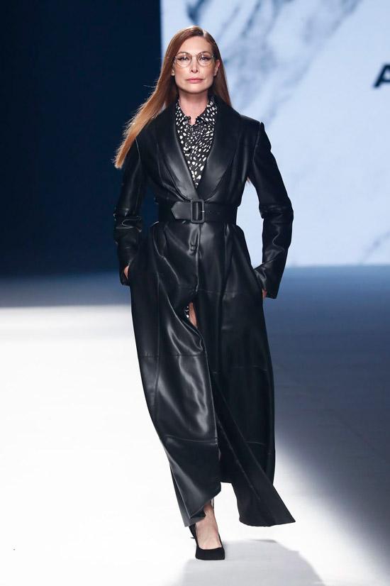 Модель в черном кожаном плаще макси с ремнем от Angel Schlesser