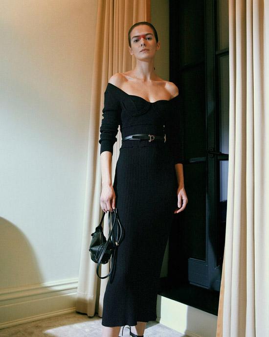 Модель в черном облегающем платье с открытыми плечами и ремнем на талии от Altuzarra