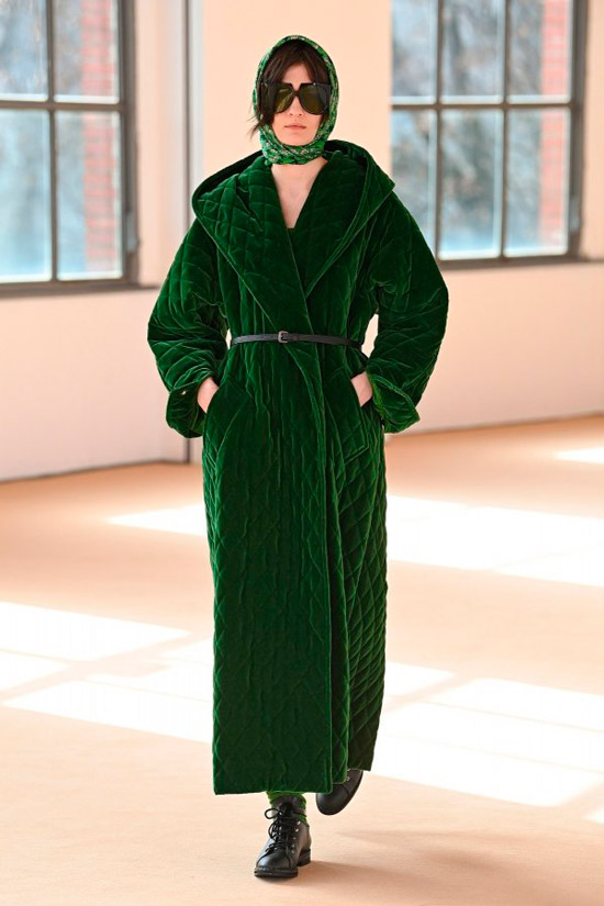 Модель в длинном зеленом пальто с тонким ремнем