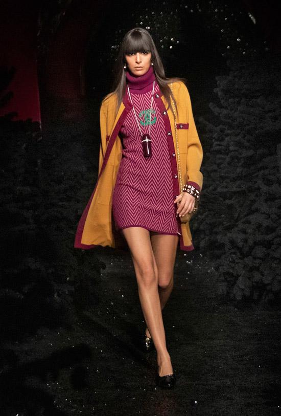 Модель в фиолетовом платье свитер мини и бежевом пальто от Chanel