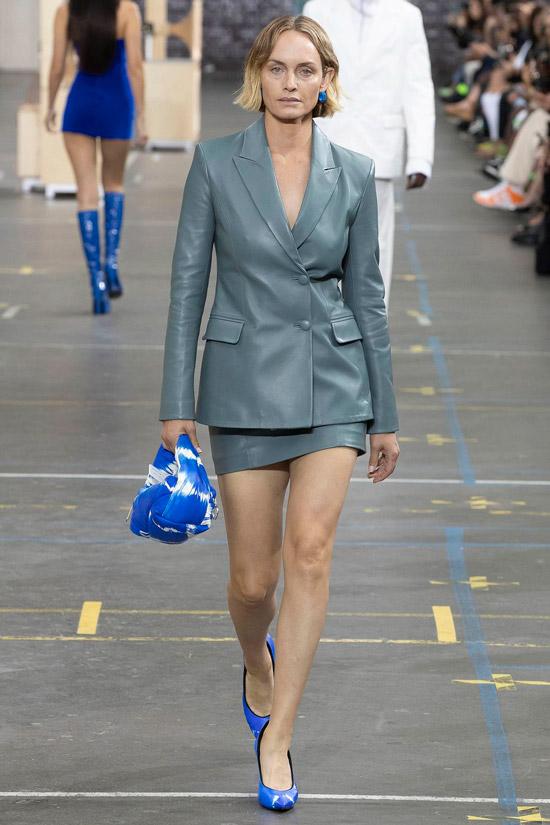 Модель в сером кожаном костюме с блейзером и мини юбкой
