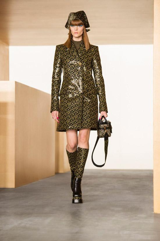 Модель в лакированном плаще мини и сапогах от Versace