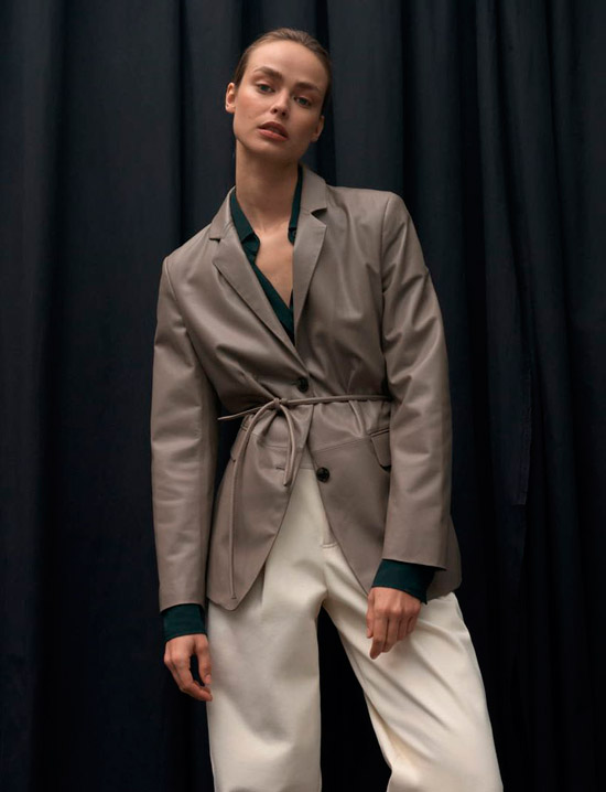 Модель в сером кожаном пиджаке с тонким поясом и белых брюках