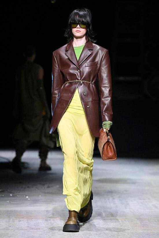 Модель в удлиненном кожаном плаще и желтой узкой юбке