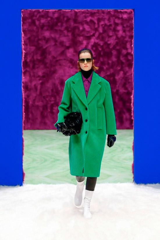Модель в зеленом пальто оверсайз и белых сапогах