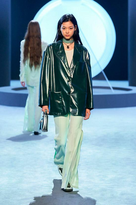 Модель в зеленой глянцевой куртке и свободных брюках