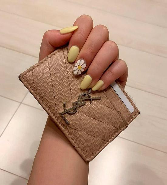 Желтый маникюр с ромашкой на ухоженных ногтях