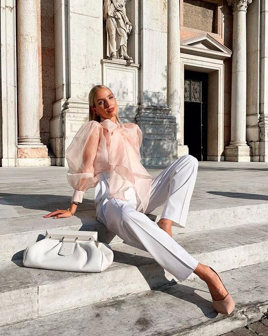 Девушка в белых брюках палаццо, воздушной блузке и бежевых туфлях