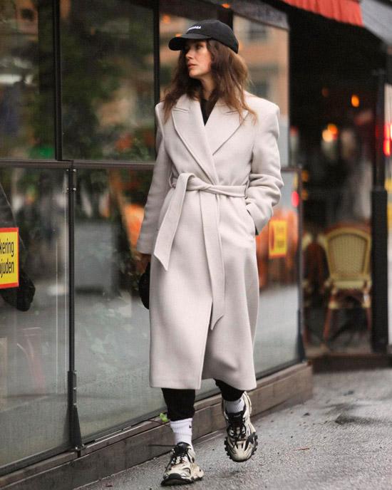 Девушка в бежевом пальто с поясом, кроссовках и черной кепке