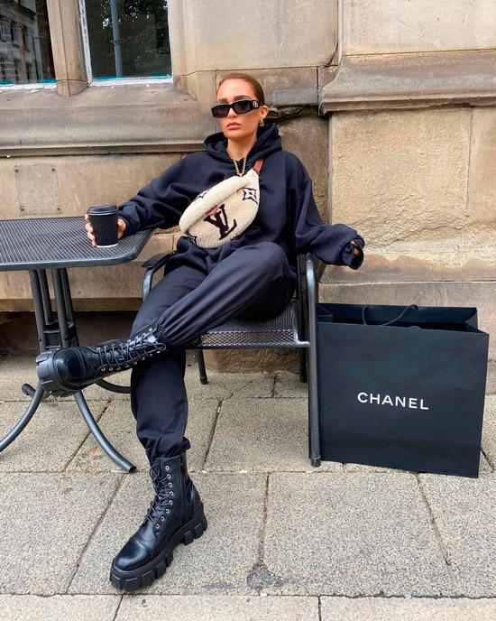 Девушка в черной толстовке, спортивных брюках и ботинках на шнуровке