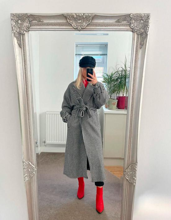 Девушка в пальто в клетку с поясом, красных ботильонах и кепке