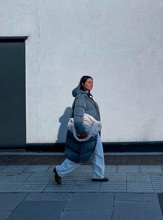 Девушка в сером пуховике оверсайз, широких штанах и ботинках